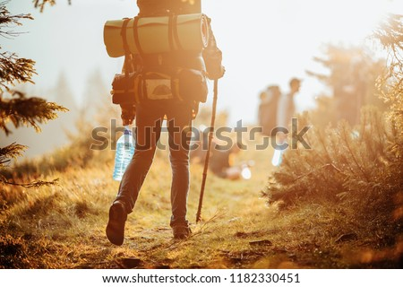 Traveller with a group hiking in the mountains at sunset.  #1182330451