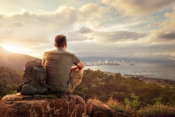 Traveller with backpack sitting on top of mountain enjoying view coast a modern city Vietnam, Nha Trang. Traveling along mountains and coast, freedom and active lifestyle concept