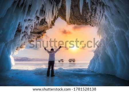 Traveller woman raise up hand freedom and enjoy view of beautiful landscape natural breaking ice in frozen cave at Lake Baikal, Siberia, Russia. Travel or Freedom concept.