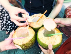 Travellers holding coconut drinks at Thai floating market