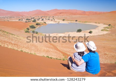 Travellers in Africa, couple on romantic vacation in Namibia, looking at beautiful Namib desert landscape