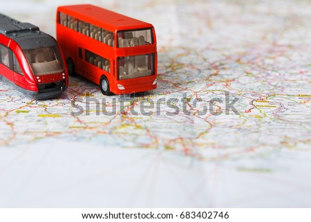 Travelling abroad background. Red doubbledecker and train on the map. Tourism, vacation and business trip concept, closeup, copy space
