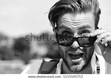 Travelling and vacations concept. Man with beard and open surprised face wears sunglasses. Tourist on blurred cityscape background, copy space. Traveller looks for tourists attractions. #1115145713