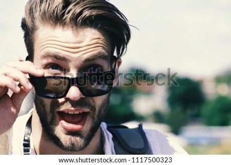 Travelling and vacations concept. Man with beard and open surprised face wears sunglasses. Tourist on blurred cityscape background, copy space. Traveller looks for tourists attractions. #1117500323