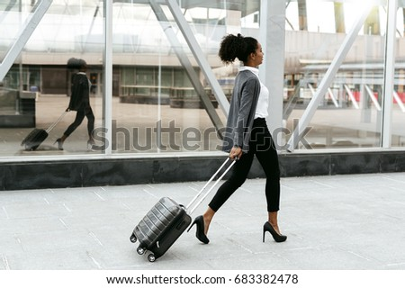 Travelling businesswoman walking with luggage at station, side view #683382478