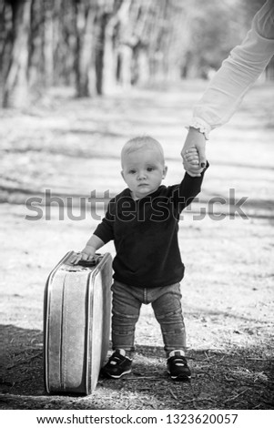 46d819a5a1e Travelling child carry suitcase on natural landscape. Travelling baby boy  travel with vintage bag with