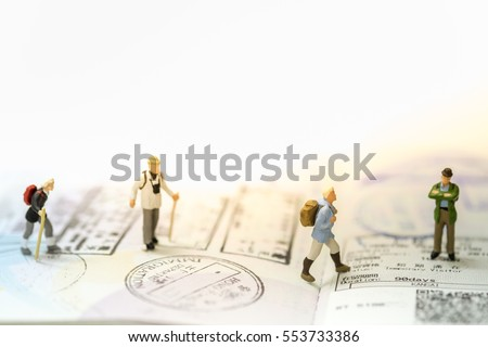 Travelling concepts. Group of traveler miniature mini figures with backpack stand and walking on passport with stamps