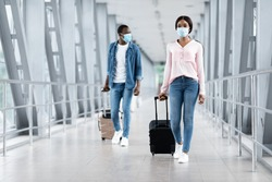 Travelling During Pandemic Concept. Black People In Masks Walking With Luggage At Airport Terminal, Copy Space