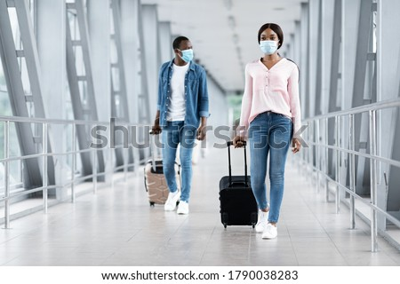 Photo of  Travelling During Pandemic Concept. Black People In Masks Walking With Luggage At Airport Terminal, Copy Space