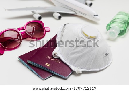 Travelling during the coronavirus outbreak. Passport with face mask, sunglasses and hand sanitizer gel. Travel and Holiday concept corona virus epidemic.  Stock fotó ©
