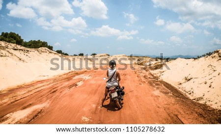 Travelling Girl is Sitting on a Motor Bike and Enjoying Landscape View on the Way to Fairy Stream of Mui Ne in Vietnam. Wanderlust Woman Driving Motorcycle to Discovering New Places in Holiday in Asia #1105278632