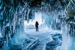 Travelling in winter, a man standing on Frozen lake Baikal with Ice cave in Irkutsk Siberia, Russia