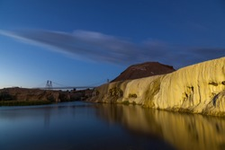 Travertine and gypsum layers left from many years of hot mineral water flow now form an embankment along the Bighorn River in Thermopolis, Wyoming. Long exposure twilight shot.