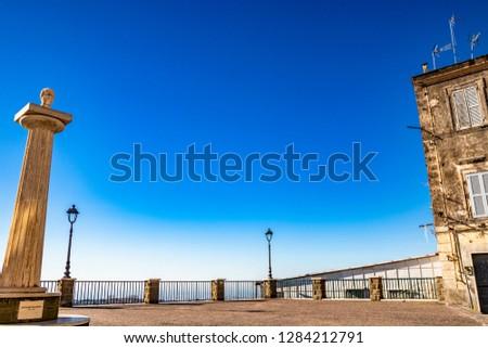 Travertine column with sculpture in memory of Giuseppe Mazzini, in the homonymous square with panoramic terrace. Ariccia, Castelli Romani, Lazio, Italy. #1284212791