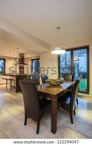Travertine house - dining room table and a kitchen in a background