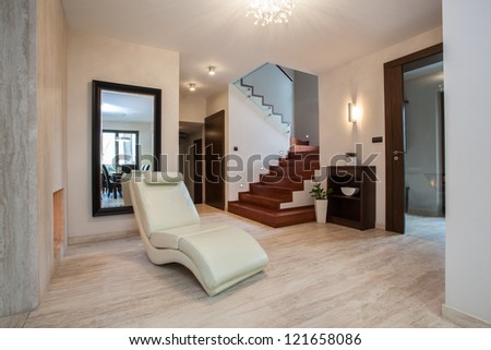 Travertine house: hallway with comfortable armchair