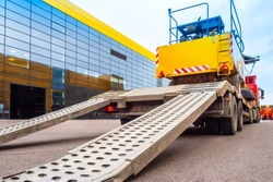Trawl transport special machines. Loading of special equipment on the tow truck with the help of ladders. Aluminum ramps for vehicles. Trawl with aluminum ramps. Transportation of oversized cargo.
