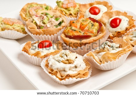 Tray full of volauvent canapes ready to serve. Volauvent is a tiny round canap made of puff pastry. The term ' vol au vent ' means ' blown by the wind ' in French.