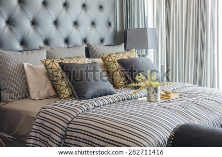 tray of book with vase of  plant on bed in luxury black bedroom at home