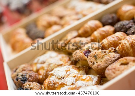 Tray of breakfast pastries taken at an angle with shallow depth of field. Wood trays of breakfast pastries set up for a birthday party on a table with red table cloth. Party food, social food.