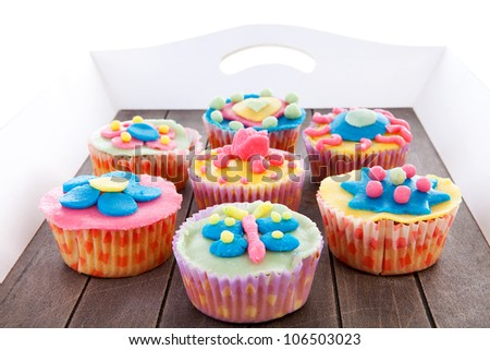 Tray with seven delicious decorated colorful cupcakes