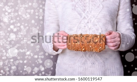 Trdelnik sprinkled with nuts and sugar is held by a woman wearing white sweater. Czech and Hungarian traditional pastry