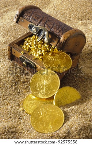treasure chest with gold coins on sandy beach