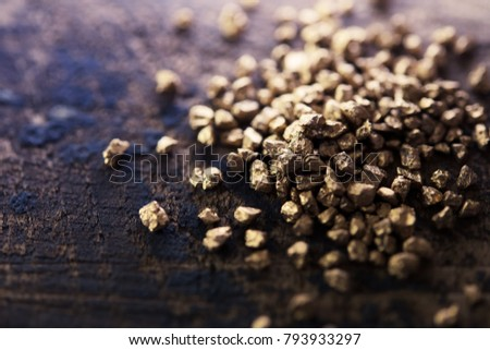 Treasure hunting. A mound of gold nuggets on a grungy rough wood work table.