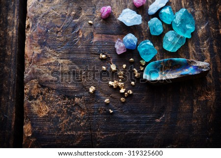 Photo of  Treasure hunting. Mining for gems. Gold and gems on rough wooden surface.