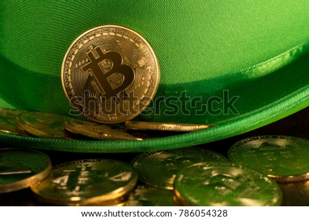 Treasure of golden bitcoins inside a green velvet hat on wooden table to celebrate luck on St Patrick's Day of March 17th