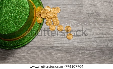 Treasure of pure gold eagle coins inside the rim of a green velvet hat to celebrate luck on St Patrick's Day of March 17th