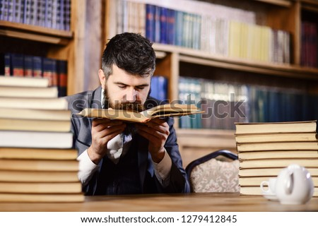 Treasures of science concept. Man with beard in classic suit, scientist or professor sniffs smell of antique book in library near pile of books, bookshelves on background, defocused.