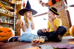 Treat or trick! Low angle shot of enjoying junior blond kids in carnival outfits, caps, with colorful treats, eating them, sitting on the floor, near the window in halloween decorated room at home