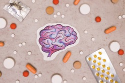 Treatment and prevention brain diseases with variety of pills: antibiotics, vitamins, painkillers, antidepressants. Drawing of brain around tablets on gray background. Top view.