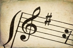 treble clef - macro of sheet music on vintage paper with added grunge texture and border