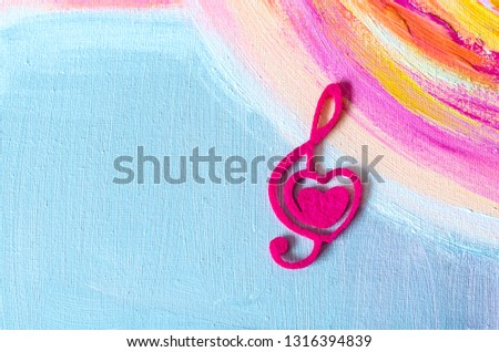 Treble clef with a heart on a beautiful background.Treble clef with a heart on a beautiful background.Photo background to Valentine's Day. Acrylic painting.