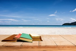 tree aged book and grunge paper on wooden platform beside tropical beach and blue sea on day noon light. background to school concept.
