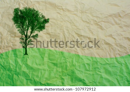 tree and green field on recycled paper