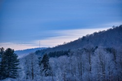 Tree Covered Hills  And Communication Tower With Snow At Red House Lake, Allegany State Park, New York
