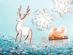 tree decorations and tangerines. wooden Christmas decorations on a light blue background. wooden patterned snowflakes, silver tinsel on a blue background. christmas carriage with deer
