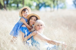 Tree females outdoors. Happy family openair portrait. Grandmother, mother and little cute child together.
