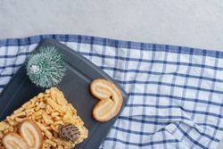 Tree, figurine, biscuit cake and flaky cookies on a board on marble background. High quality photo
