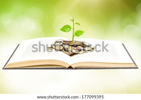 tree growing from book with coins / A big open book with coins and tree. \