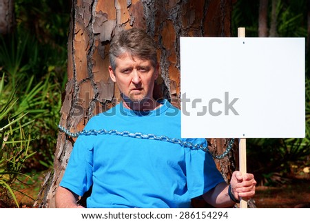 Tree hugger eco warrior man holding up blank sign and he is chained to a tree to protest deforestation while trying to save this tree\'s life