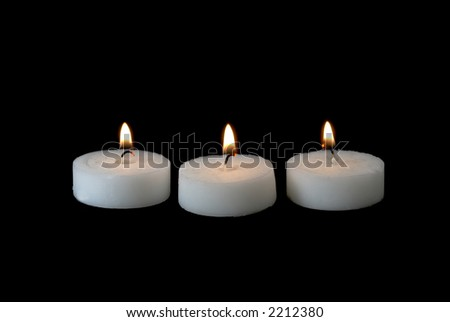 Tree lit candles on a black background