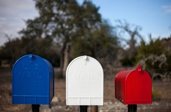 Tree mailboxes painted in red white and blue with a rural setting in background / Communication concept