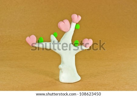 Tree of love made from plasticine pink heart white trunk green leaves on brown paper background