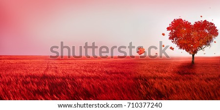 Photo of Tree of love. Red heart shaped tree at sunset. Beautiful landscape with red tree and falling leaves.Love background