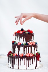 Tree story cake with hand putting cherry on the top