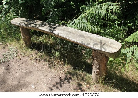 Tree stump bench on a trail in the woods stock photo for Tree trunk garden bench